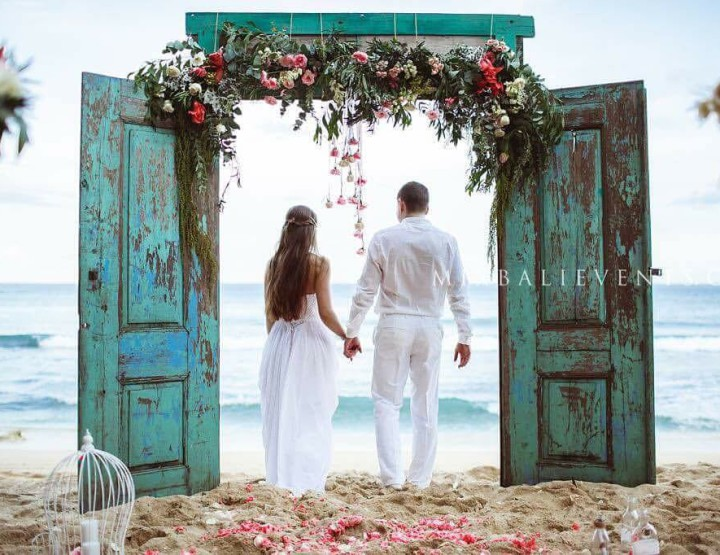 Wedding with the Stylish Arch made of the Antique doors on the beach with white sand